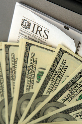 Stack of hundred dollar bills laid out on top of IRS form,