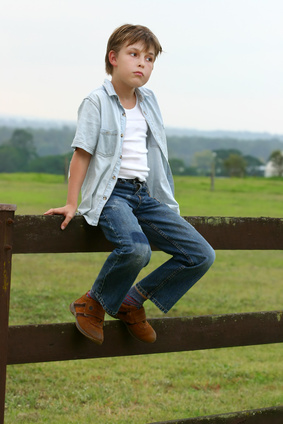 Farm boy sitting on a wooden fence in late afternoon dusk.